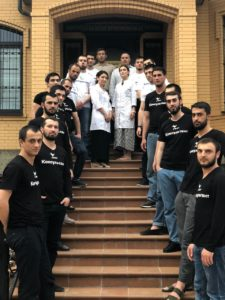 двадцать два человека 12 из которых в чёрных футболках консультанты (шесть слева, шесть справва) и десять из них в светлых одеждах из которых восем парни и две девушки в халатах, шесть парней в белых футболках, мужчина в тюбетейке и рубашке, и один мужчина в поло
